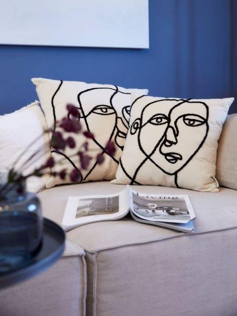 Salon z niebieską ściną, białą kanapą oraz dwoma poduszkami dekoracyjnymi