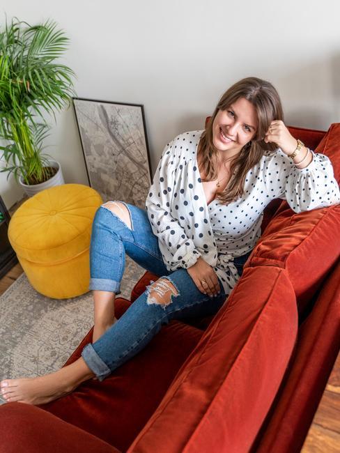 Joanna Banaszewska siedząca na czerwonej kanapie w salonie