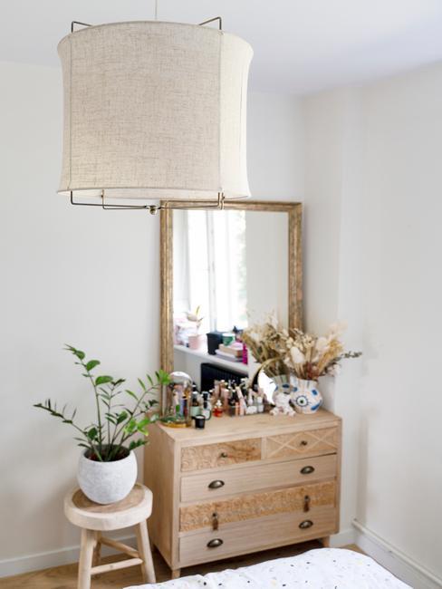 Fragment białej sypialni z boho, drewnianą komoda, lustem oraz rośliną na stoliku