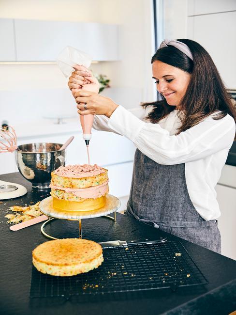 Kobieta ozdabiająca tort w białej kuchni z czarnym blatem