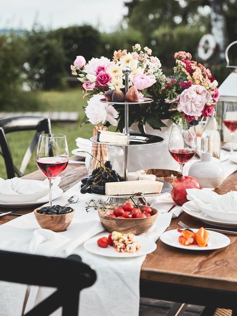 Udekorowany stół na przyjęcie z użyciem kwiatów, pater oraz zastawy