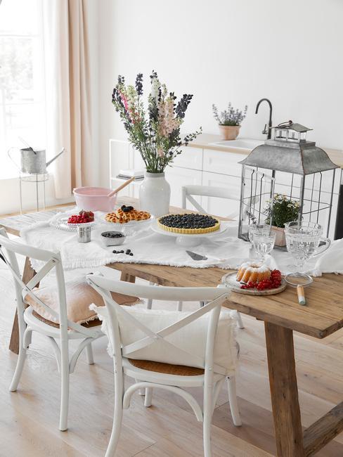 Drewniany stół z białym obrusem, wazonem kwiatów, klatką dekoracyjną oraz słodyczami