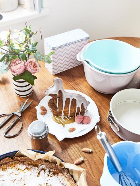 Ciasto wielkanonce w kształcie zajączka na drewnianym stole, obok akcesoriów kuchennych i wazonu
