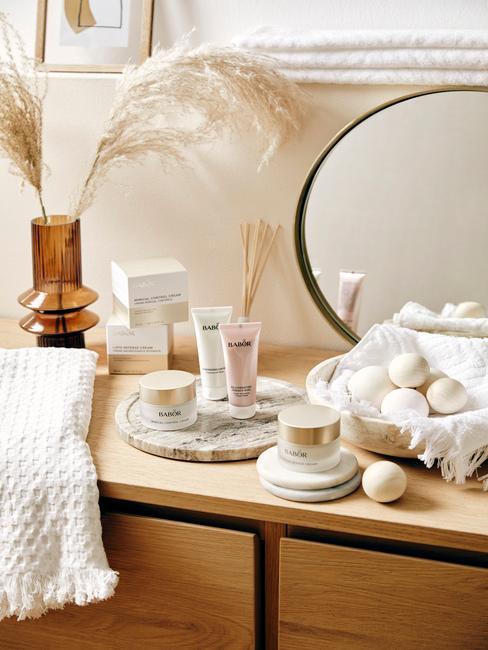 Drewniany blat w łazience z lustem, wazonem z suszonymi kwiatami oraz kosmetykami na marmurowej tacy