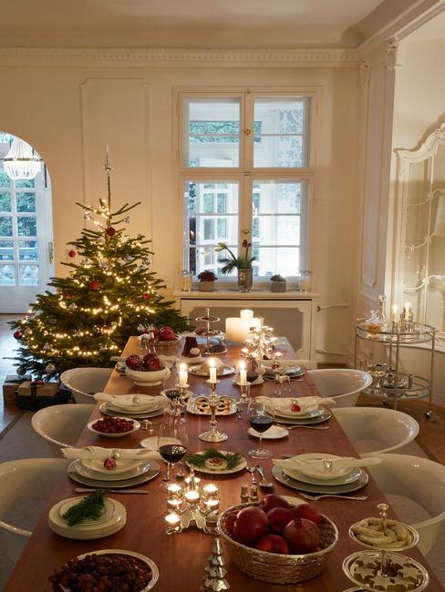 Wnętrze jadalni z udekorowaną choinką i parapetem oraz stołem wigilijnym z zastawą i dekoracjami