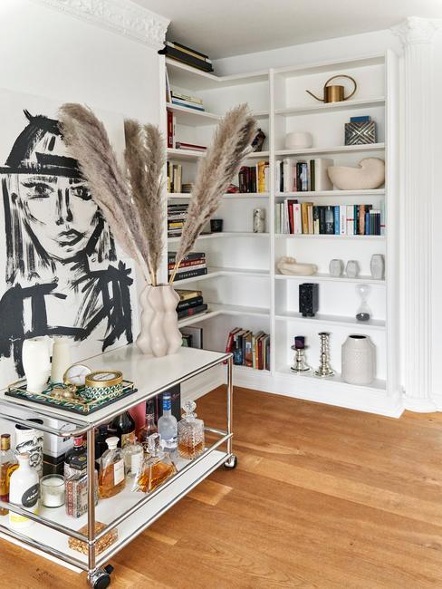 Białe wnętrze salonu z półką, wóżkiem na którym jest wazon z trawą pampasową