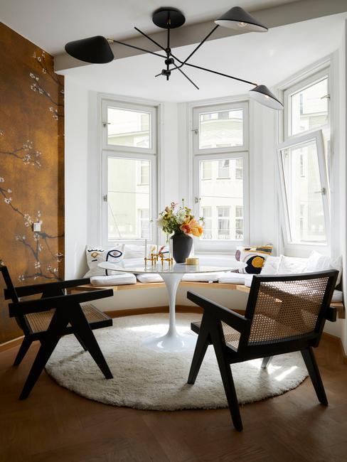 Okrągły stół w oknie wykuszowym, modne krzesła z plecionki wiedeńskiej