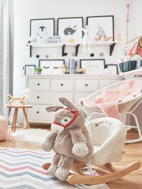 Biały pokój dziecięcy z komodą, dywanem, krzesłem i dekoracjmi ściannymi