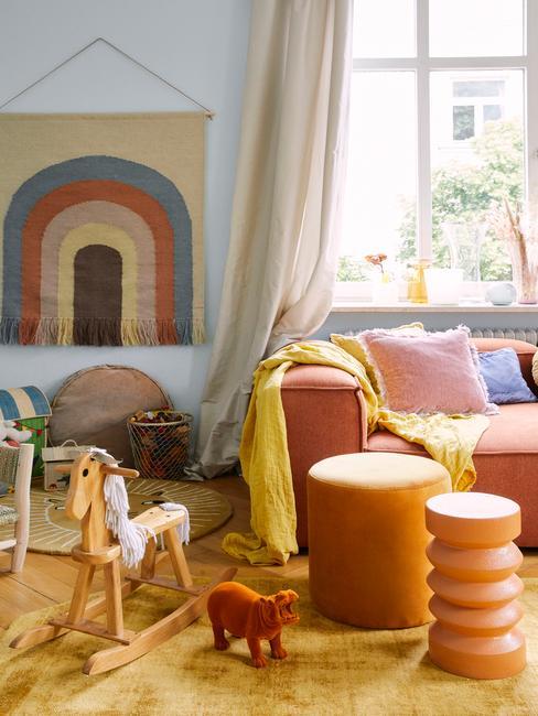 Fragment pomieszczenia z sofą i pufami, oraz kącikiem zabaw