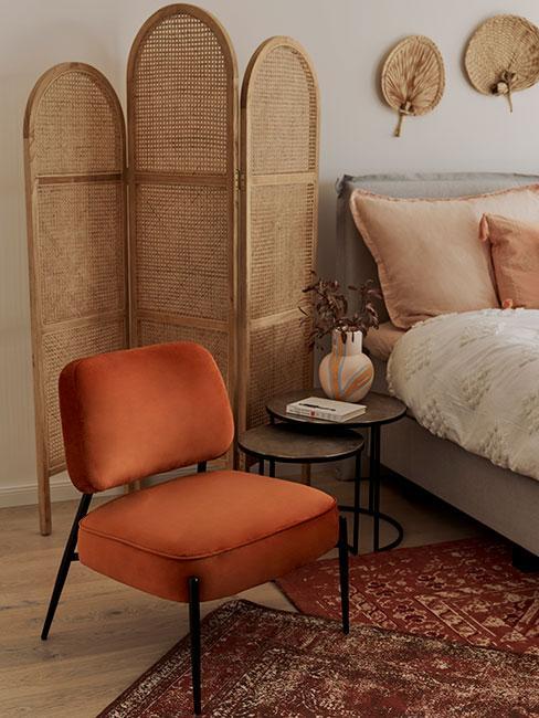 Pomarańczowe tapicerowane krzesło obok łóżka