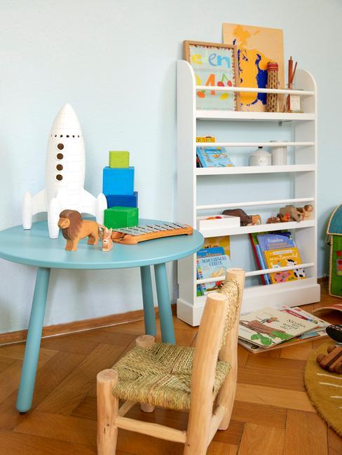 Pokój dziecięcy z niebieskim stolikiem, białą półką i zabawkami