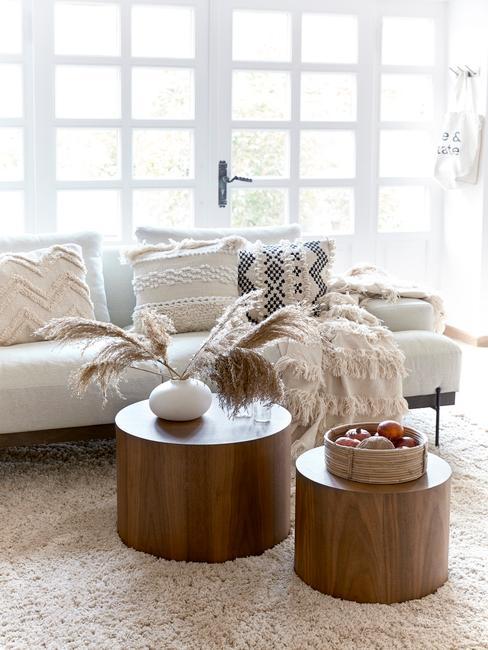 Wnętrze salonu z szafą sofą, poduszkami, drewnianymi stolikami oraz dekoracjami z trawy pampasowej
