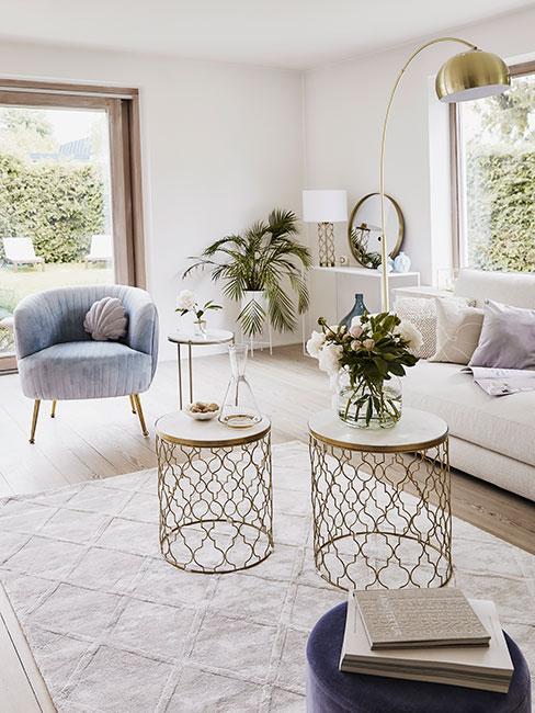 Jasny salon z błękitnym fotelem z aksamitu i ażurowymi stolikami