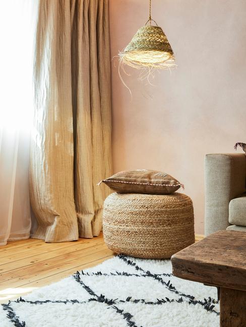 Wnętrze w stylu boho z jutowym pufem, poduszką, biało - czarnym dywanem oraz lampą
