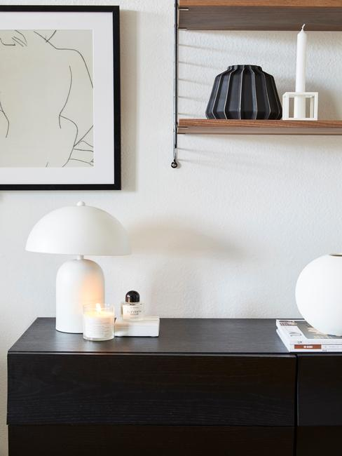 Zbliżenie na czarny blat biurka z lampą, świeczami oraz wiszącą nad nią półką