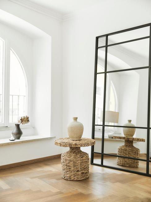 Białe wnętrze z stolikiem rattanowym, wazoną oraz lustrem