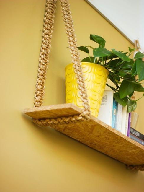 Żółta ściana, na której wisi własnoręcznie wykonana półka z dekoracjami