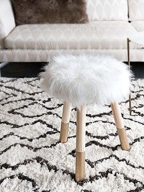 Futrzany stołek DIY w salonie, postawiony na czarno-białym dywanie