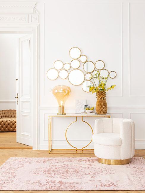 Złota konsola przy różowym dywanie i kremowym fotelu
