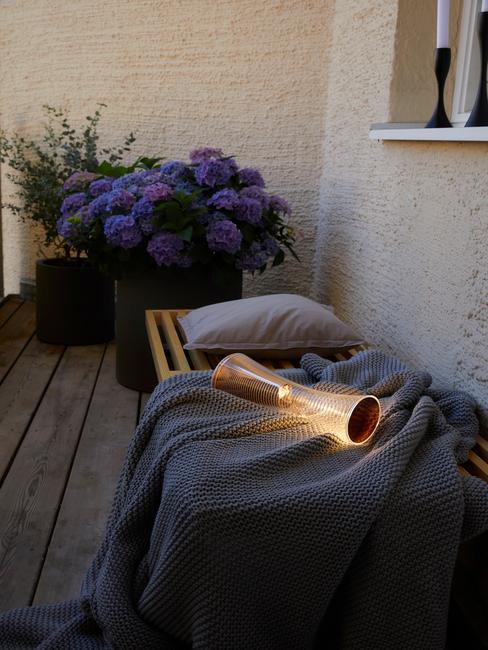 Fragment balkonu z roślinami doniczkowymi oraz ławką na której jest koc oraz poduszką