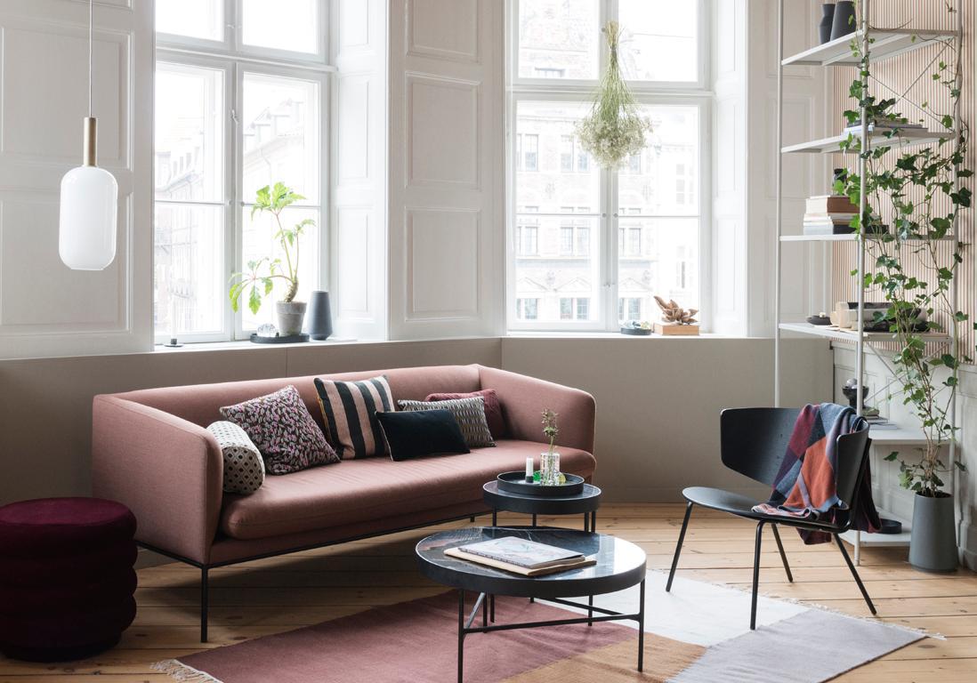 salon avec petit canapé rose, coussins décoratifs, étagère en métal et chaise en bois noir