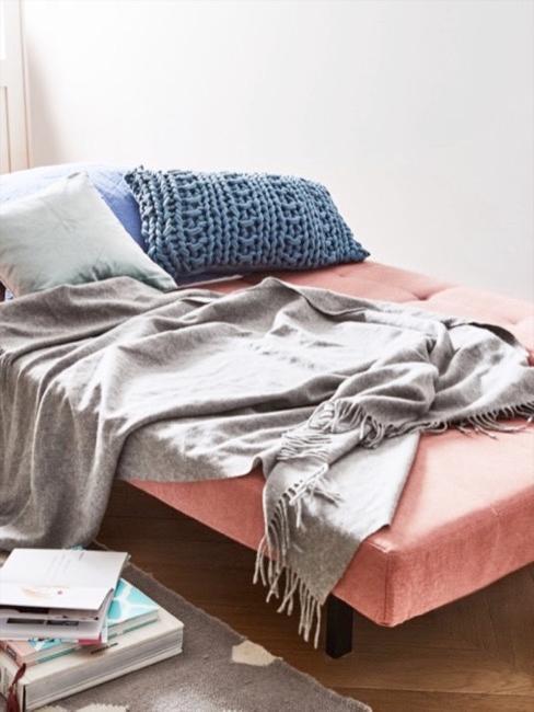 Futon Sofa in Rosa, ausgeklappt, darauf Kissen und eine Decke