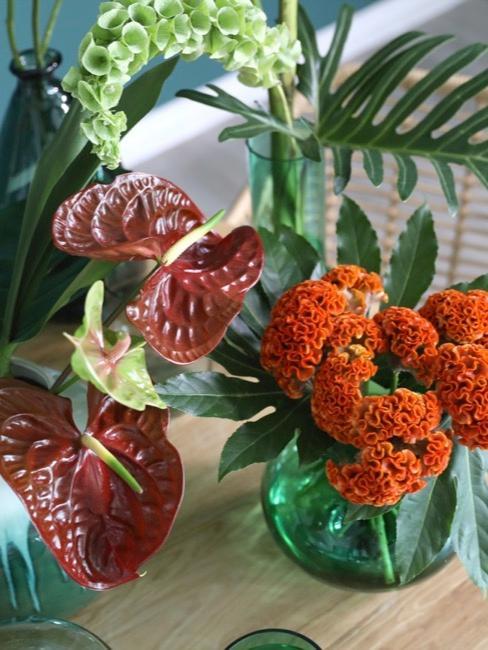 Pomarańczowe sztuczne kwiaty w zielonych wazonach na stole