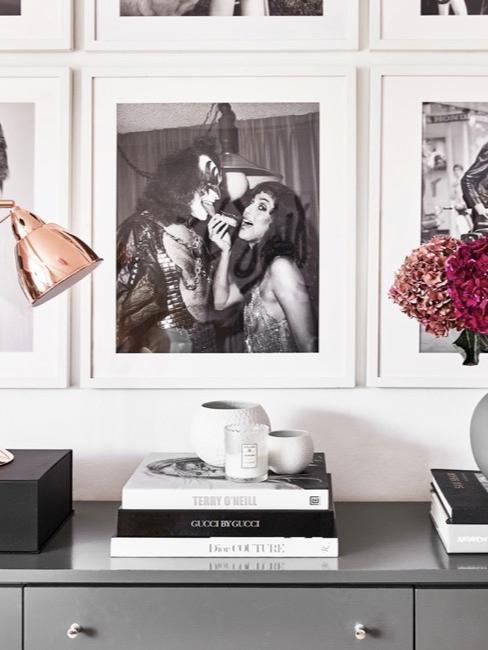 Sztuczne kwiaty na kredensie z książkami i lampką poniżej obrazków