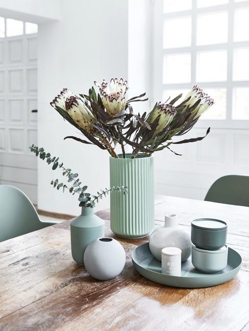 Elementi decorativi verde menta su un tavolo da pranzo