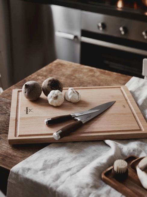 Nahaufnahme Küchenamaturen mit Holzbrett, Knoblauch und Messern