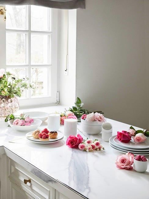 Rosa und pinke Rose liegen in der Küche auf der weißen Kücheninsel