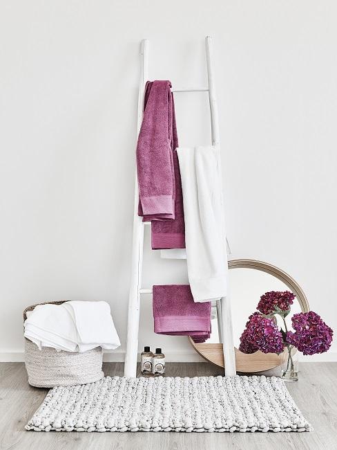 Eine weiße Holzleiter steht im Bad mit bunten Handtüchern.