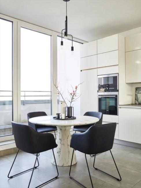 Weiße Lackküche mit runden Marmortisch und schwarzen Stühlen im Vordergrund