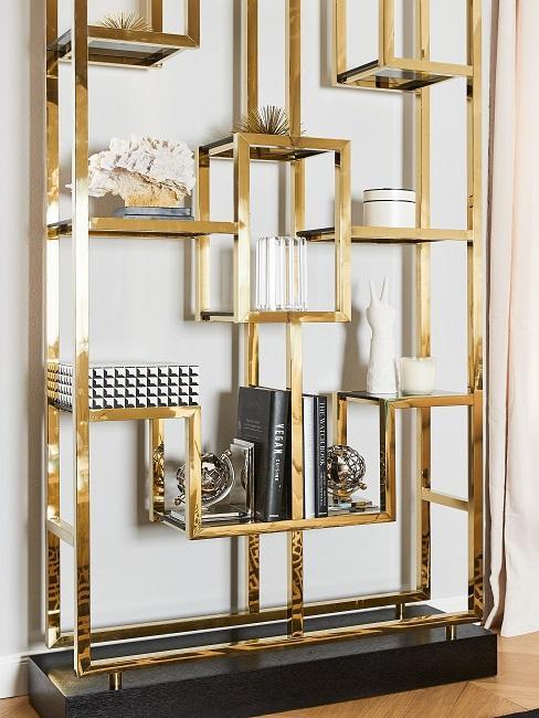 Goldfarbenes Regal mit schönen Buchstützen und Büchern