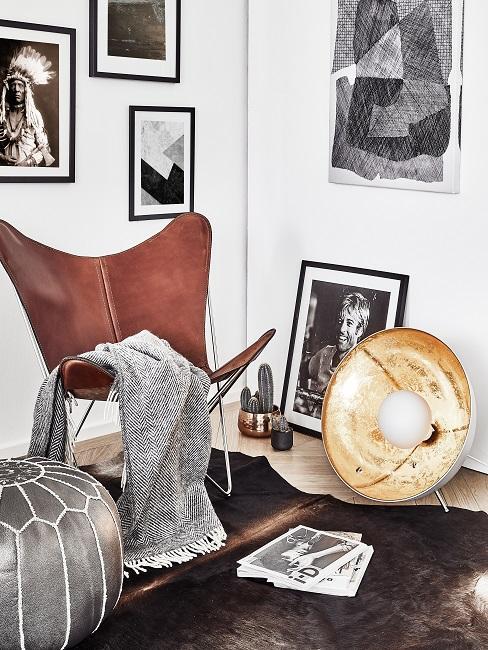 Leeshoek met een leren fauteuil en een plaid, naast een zilveren poef
