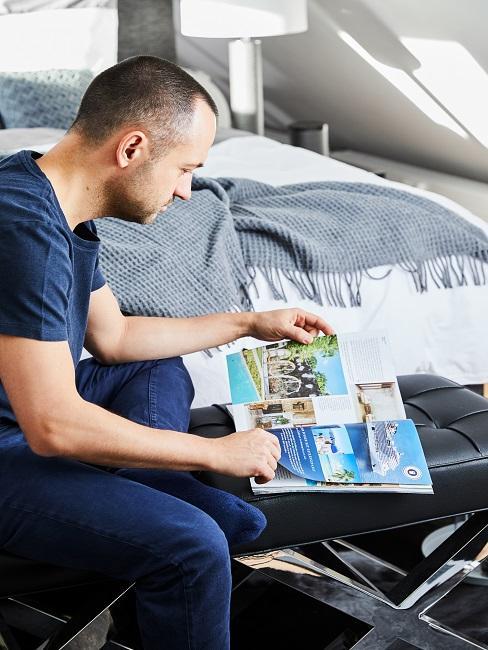 Man zittend op een bank in een mannenkamer kijkend naar een boek met foto's