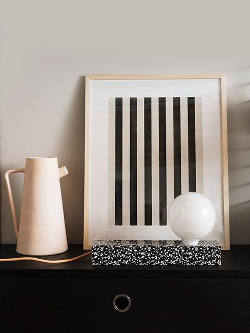 Beżowy dzbanek z kamionki i oprawiony dreuk przedstawiający czarne równoległe linie w minimalistycznym stylu