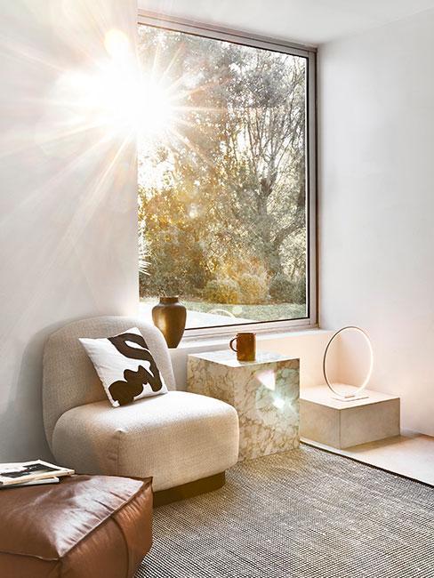 jasny pokój z minimalistycznym beżowym fotelem tapicerowanym i marmurowym stolikeim