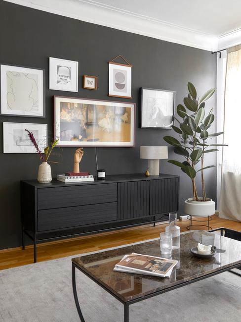 Czarna ściana w dużym pokoju z obrazkami w ramkach