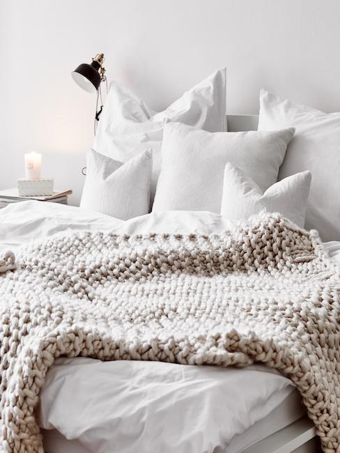 Lit avec parure blanche et couverture tricotée beige