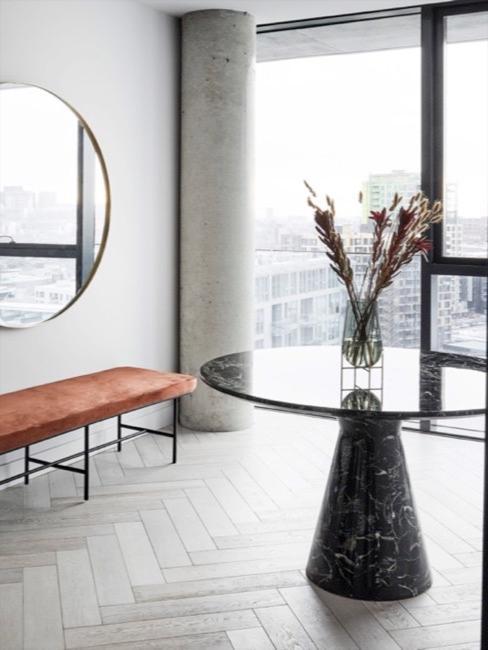 Salon z surowym wykończeniem, dużym lustrem na ścianie, pomarańczową ławką z aksamitu  oraz marmurowym okrągłym stołem