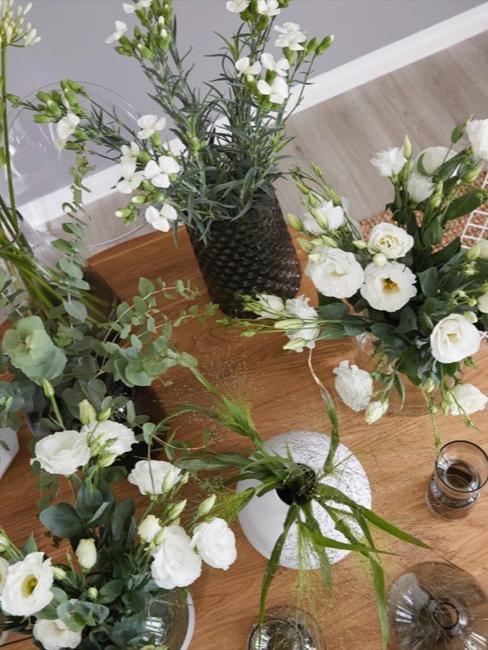 mesa de madera con ramos de flores blancas