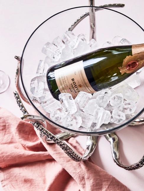 cubitera de vidrio con hielo y una botella de champán