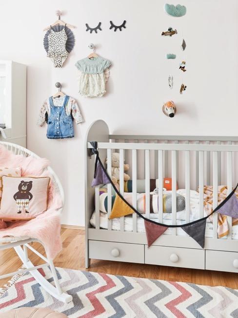 Chambre pour bébé très colorée avec un lit bébé et un fauteuil à côté, ainsi que de la décoration pour bébé sur le mur