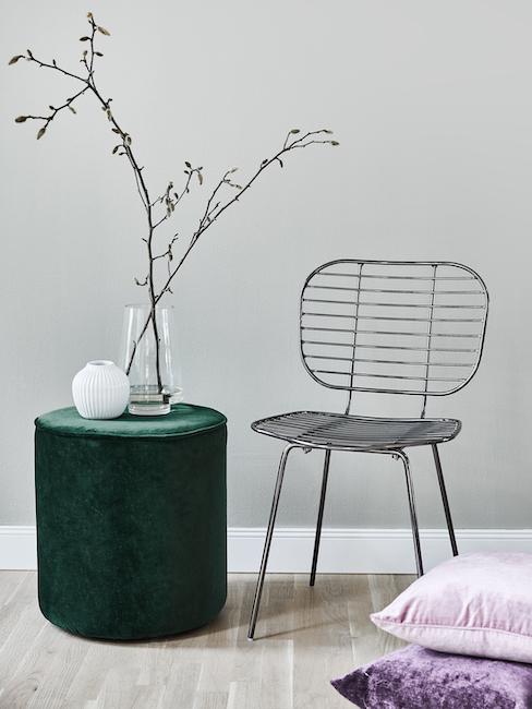 Groene poef naast zwart metalen stoel