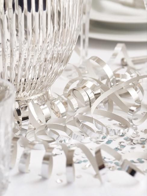 Udekorowany stół ze srebrnymi dekoracjami oraz elegancką szklanką