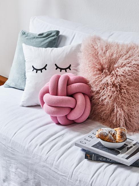 Poduszki o różnych teksturach, wzorach i kolorach na kanapie