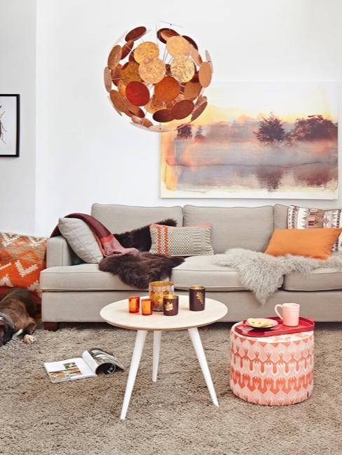 Salon z beżową szafą, na której leżą poduszki w jesiennych kolorach.