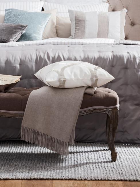 Sypialnia w stylu barokowym z ławką drewnianą i łóżkiem kontynentalnym