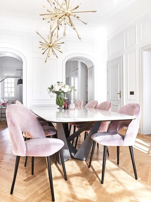 comedor grande con techo alto, lámparas de techo doradas y sillas rosas